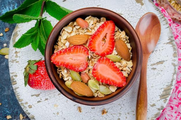 Gesundes frühstück selbst gemachtes granola mit frischen erdbeeren