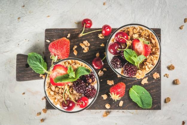 Gesundes frühstück. sommerbeeren und früchte. hausgemachter griechischer joghurt mit müsli, brombeeren, erdbeeren, kirschen und minze. auf weißer konkreter steintabelle in den gläsern. ansicht von oben