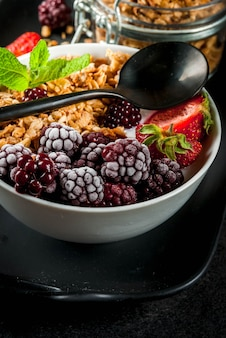 Gesundes frühstück. sommerbeeren und früchte. selbst gemachter griechischer joghurt mit granola, brombeeren, erdbeeren und minze. schwarzer steintisch, mit den zutaten.