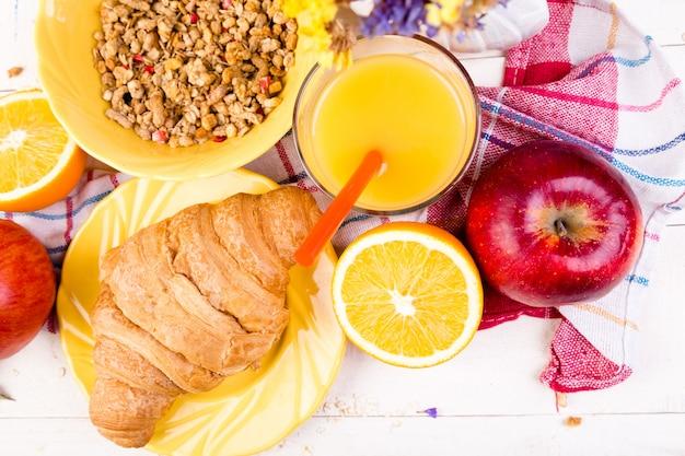 Gesundes frühstück. verschiedenes sortiment. orangensaft, müsli, croissant und obst.