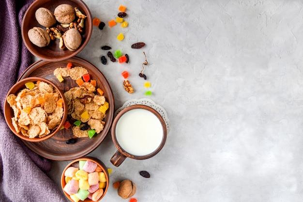 Gesundes frühstück (weizenflocken, walnüsse, kandierte früchte, rosinen, milch)