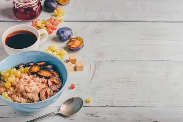 Gesundes frühstückskonzept. brei mit frischen pflaumen, grünen trauben und einer tasse kaffee. zutaten über holzhintergrund.