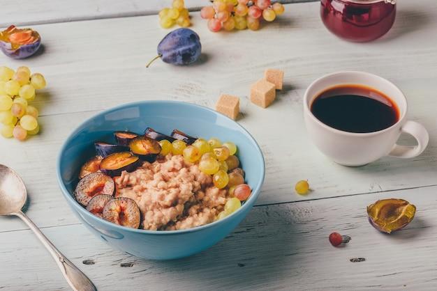 Gesundes frühstückskonzept. brei mit frischen pflaumen, grünen trauben und einer tasse kaffee. zutaten über holztisch.
