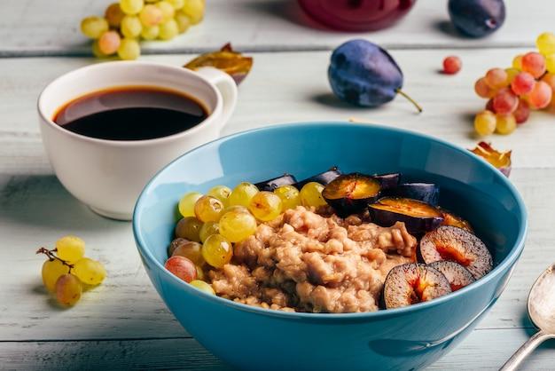 Gesundes frühstückskonzept. brei mit frischen pflaumen, grünen trauben und einer tasse kaffee.