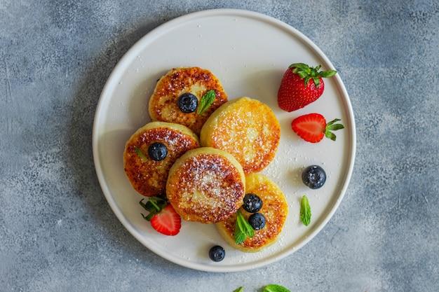 Gesundes frühstückskonzept mit kaffee. käsepfannkuchen mit erdbeere, heidelbeere, minzblatt auf weißem keramikteller mit gabel und messer auf grau serviert