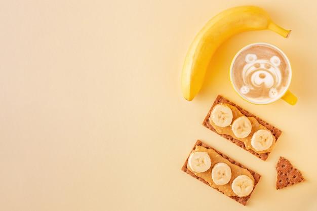 Gesundes frühstückskonzept mit latte und knäckebrot mit erdnussbutter auf gelb