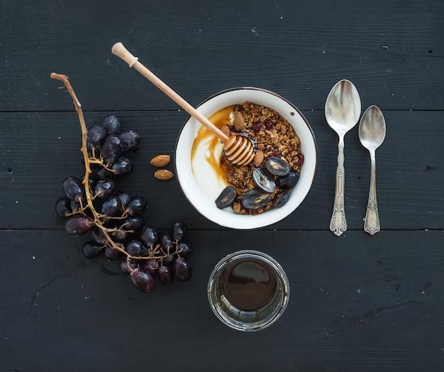 Gesundes frühstücksset. schüssel hafergranola mit joghurt, frischen trauben, mandel und honig über schwarzem hölzernem hintergrund