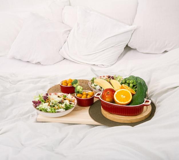 Gesundes gesundes frühstück mit obst auf einem tablett im bett. das konzept der gesunden ernährung.