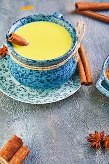 Gesundes getränk der goldenen latte-kurkuma in einer blauen tasse.