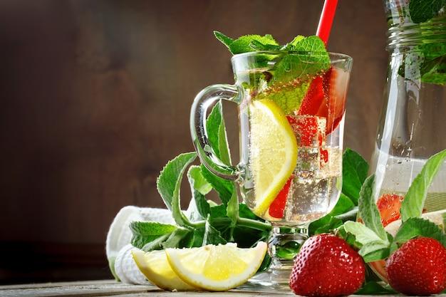 Gesundes getränk des frischen sommers mit zitrone und erdbeeren mit eis.