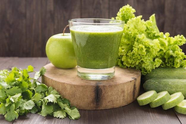 Gesundes grünes gemüse und grüner frucht smoothie auf rustikaler hölzerner tabelle