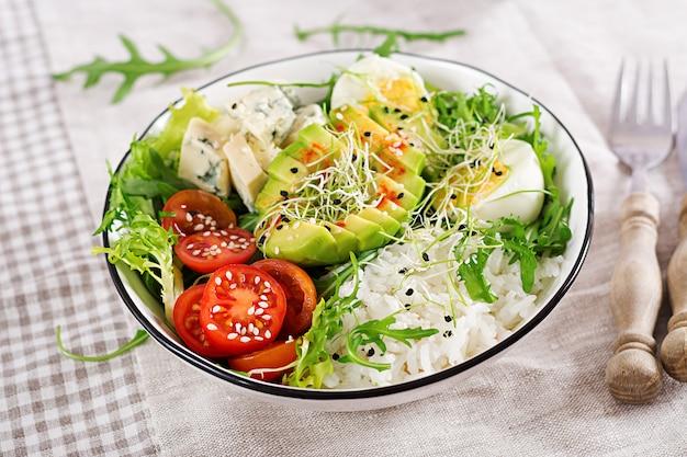 Gesundes grünes vegetarisches buddha-schüsselmittagessen mit eiern, reis, tomate, avocado und blauschimmelkäse auf tabelle