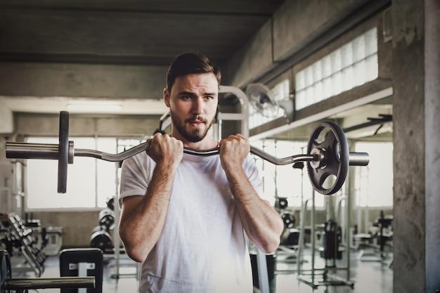 Gesundes halten des dummkopftrainings der nahaufnahmemannes und gebäudekörper an der turnhalleneignung