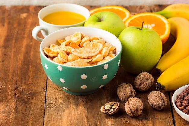 Gesundes hausgemachtes frühstück mit müsli, äpfeln, frischen früchten und walnüssen