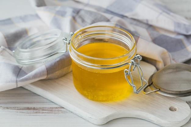 Gesundes hausgemachtes ghee oder geklärte butter in einem glas auf weißem holztisch