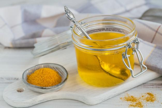 Gesundes hausgemachtes ghee oder geklärte butter in einem glas und kurkumapulver auf weißem holztisch. gesundes ayurveda-lebensmittelkonzept.