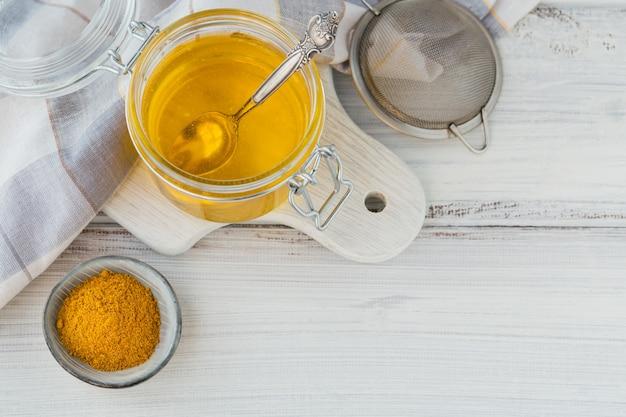 Gesundes hausgemachtes ghee oder geklärte butter in einem glas und kurkumapulver auf weißem holztisch
