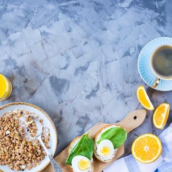 Gesundes herzhaftes frühstück - müsli, sandwich mit ei, kaffee, orange und saft
