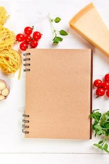 Gesundes italienisches essen, das leeres notizbuch kocht