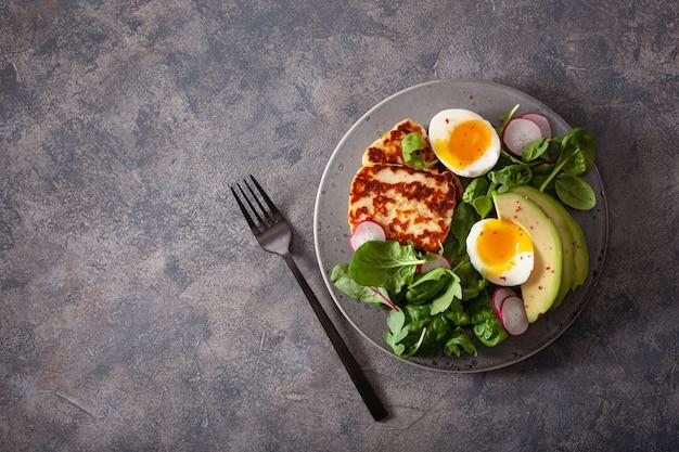 Gesundes keto-paläo-diät-frühstück: gekochtes ei, avocado, halloumi-käse, salatblätter