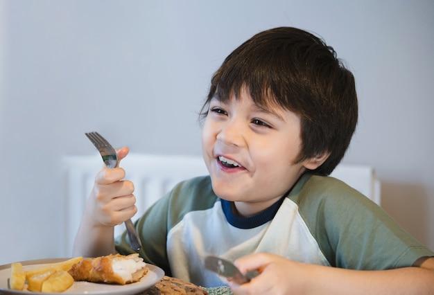Gesundes kind, das gebratenes geschlagenes fischfilet für brunch isst