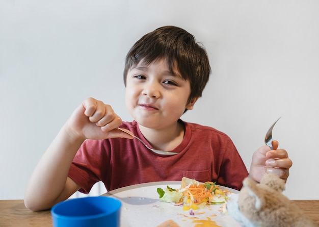 Gesundes kind, das gemischten gemüsesalat für seine mahlzeit isst,
