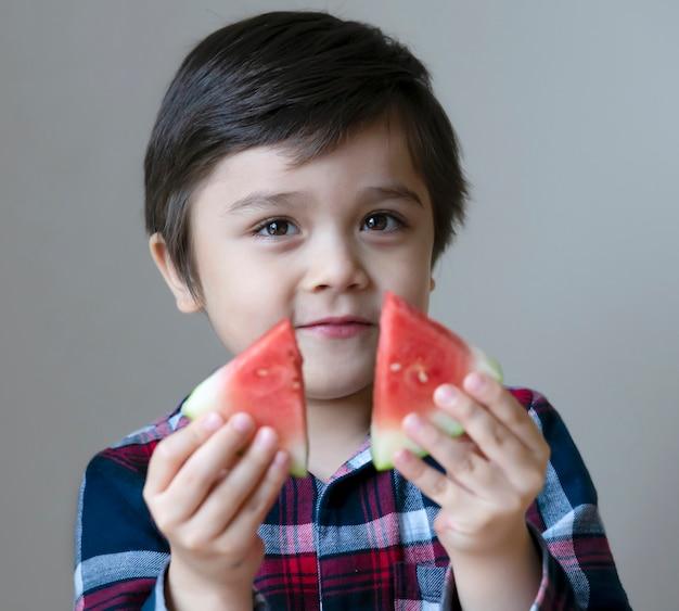 Gesundes kind des porträts, das frische wassermelone isst