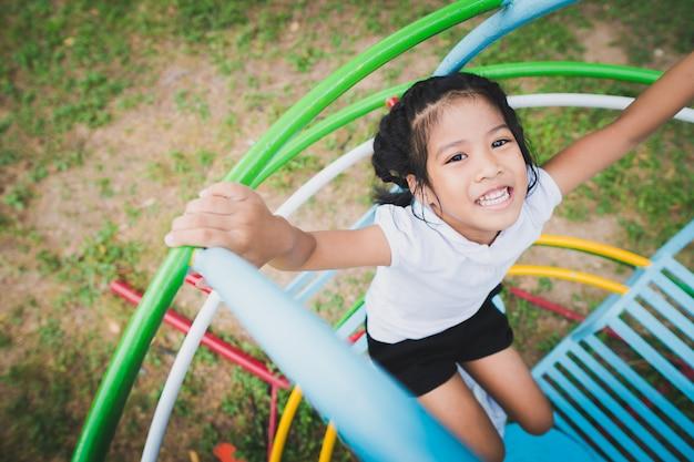 Gesundes kleinkind spielt im hinterhof, glücklich mit dem schwingen, den schaukelpferden, den diawagen.
