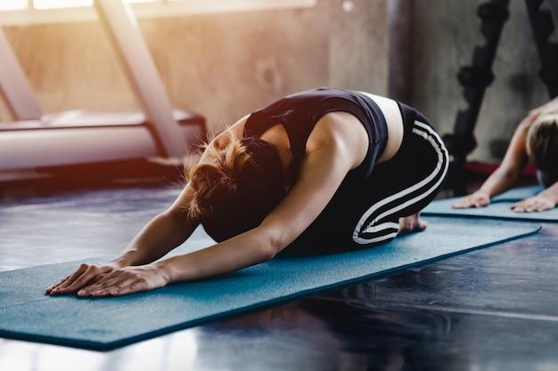 Gesundes körpertraining des asiatischen lebensstils der jungen frau in der turnhalle, sportart-yogakonzept