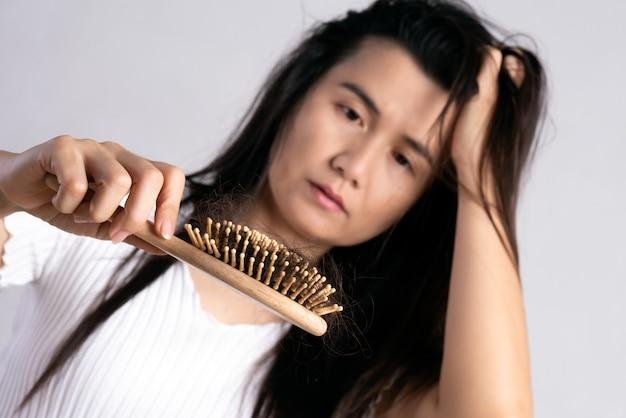 Gesundes konzept. frau zeigen ihre bürste mit beschädigten langen haarausfall