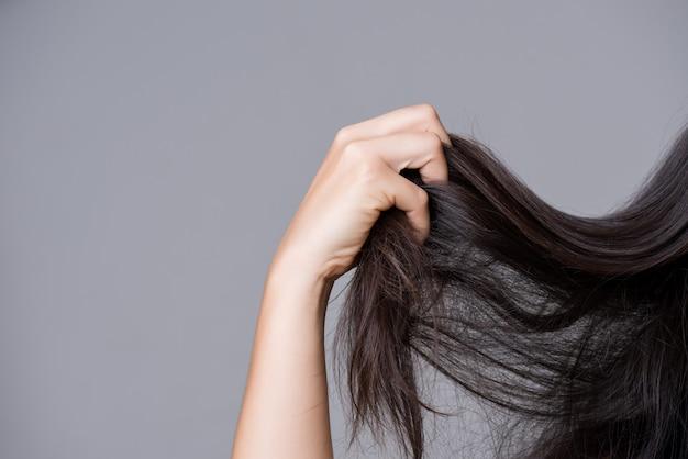 Gesundes konzept frauenhand, die geschädigtes langes haar anhält