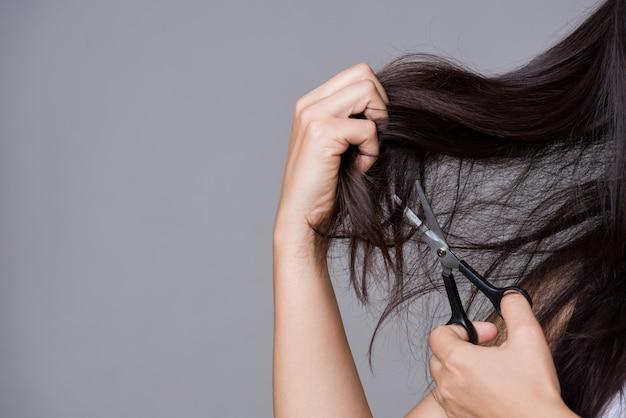 Gesundes konzept frauenhand, die scheren hält und ihr beschädigtes langes haar schnitt