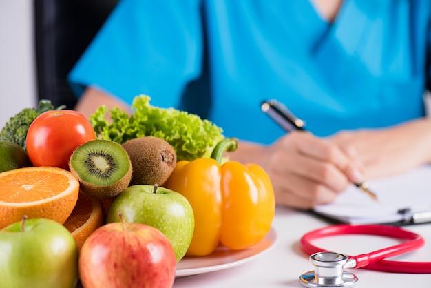 Gesundes konzept, frischgemüse und früchte mit dem stethoskop, das auf schreibtisch doktors liegt.