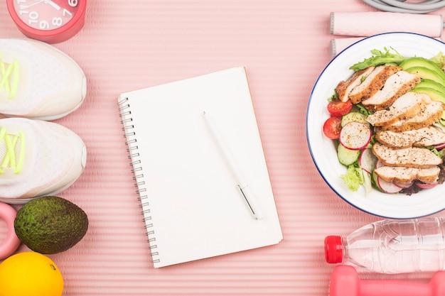 Gesundes konzept mit ernährungsnahrung in der brotdose und fitnessausrüstungen mit frau, die zeit schreibt, um auf tagebuchbuch gesund zu werden