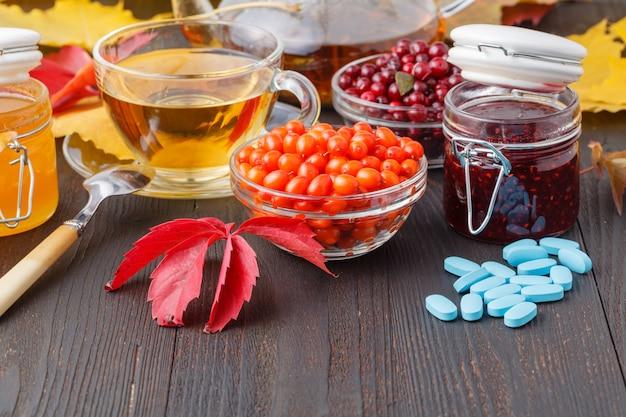 Gesundes konzept. winterbeerentee mit preiselbeeren, honig und thymian in einer glasschale auf holztisch. alternativ zur traditionellen medizin