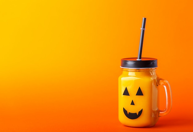 Gesundes kürbis- oder karottengetränk halloweens im glasgefäß mit furchtsamem gesicht auf einem orange hintergrund mit kopienraum