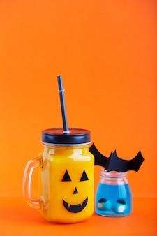 Gesundes kürbis- oder karottengetränk halloweens im glasgefäß mit furchtsamem gesicht auf einem orange hintergrund