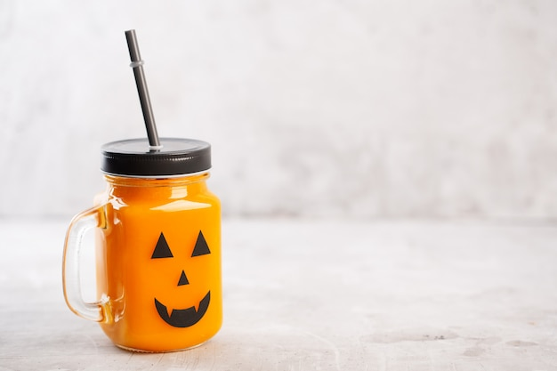 Gesundes kürbis- oder karottengetränk halloweens im glasgefäß mit furchtsamem gesicht auf grau