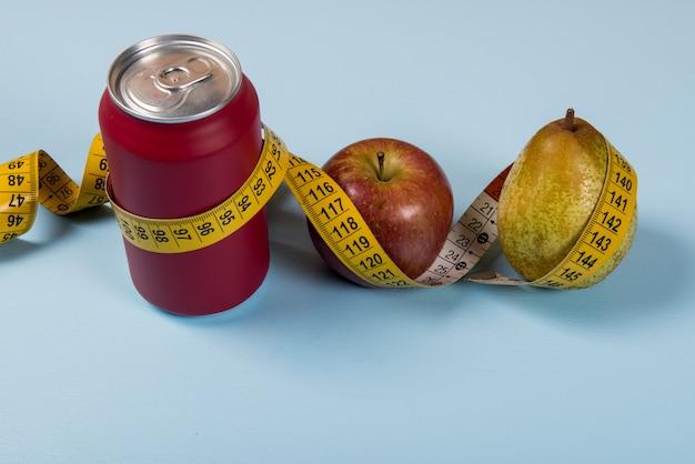 Gesundes leben kontrastiert mit dose soda und obst mit einem maßband