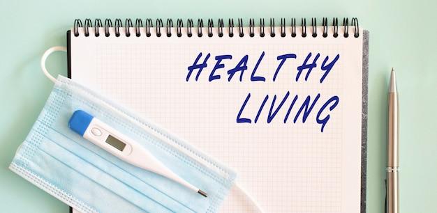 Gesundes leben text in einem notizbuch. eine medizinische schutzmaske und ein thermometer befinden sich auf dem notebook.