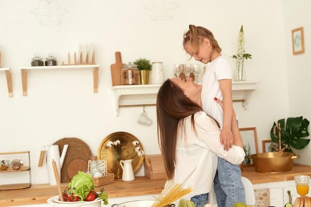 Gesundes lebenskonzept der glücklichen familie. mama umarmt ihre tochter beim kochen in der küche.