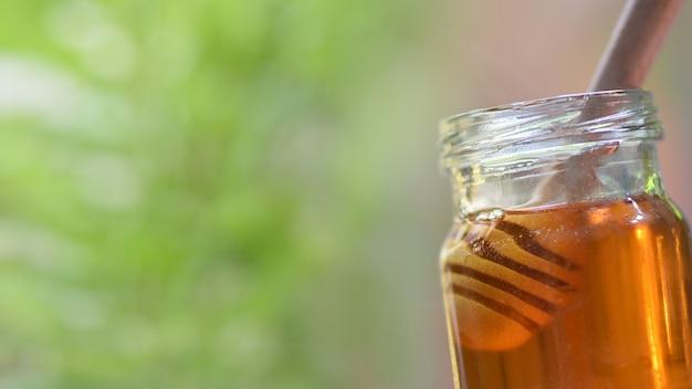 Gesundes lebensmittel des frischen honigs / abschluss oben des gelben süßen honigs im glas mit hölzernem schöpflöffel