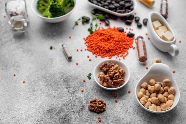 Gesundes lebensmittel des strengen vegetariers auf einem konkreten hintergrund mit kopienraum. nüsse, bohnen, gemüse und samen