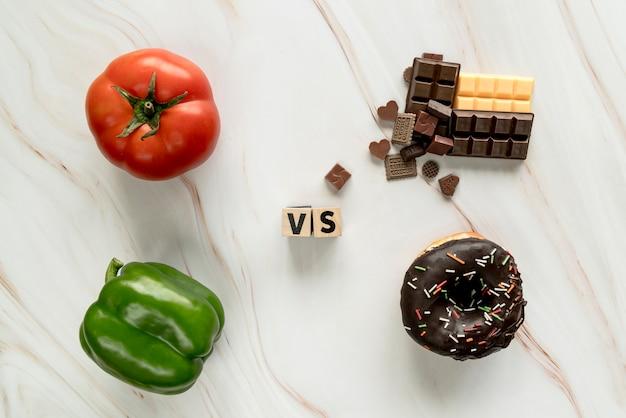 Gesundes lebensmittel gegen ungesundes lebensmittelkonzept über strukturiertem hintergrund