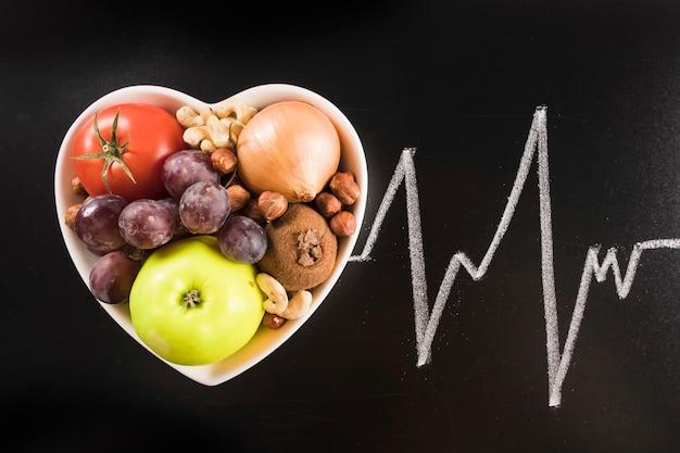 Gesundes lebensmittel im herzformbehälter mit kreide gezeichnetem herzimpuls auf tafel