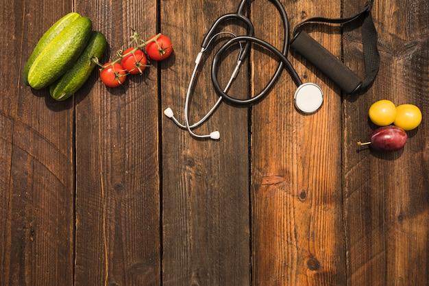 Gesundes lebensmittel mit stethoskop- und eignungsbügel auf hölzernem hintergrund