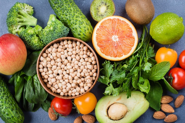 Gesundes lebensmittel sauberes konzept. rohe früchte, gemüse, nüsse, getreide auf konkretem steintabellenhintergrund