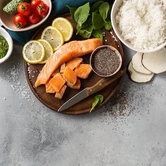 Gesundes lebensmittelkonzept des strengen vegetariers bestandteile für das kochen der sackschüssel mit draufsicht der lachse, der avocado, des gemüses und des chia samens