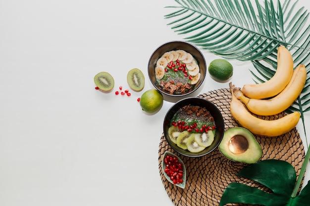 Gesundes lebensmittelkonzept. draufsicht auf tisch mit smoothie-schalen. teller mit kiwi, müsli, granat, chia, avocado.