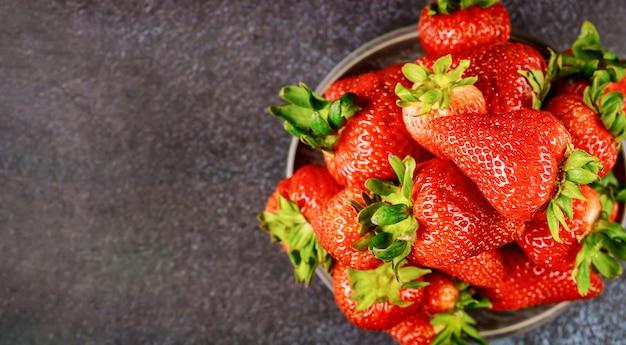 Gesundes lebensmittelkonzept erdbeeren im teller auf dunkler oberfläche.